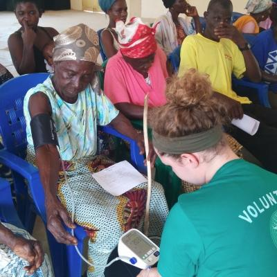 A student doing a Nursing internship in Ghana with Projects Abroad treats a local woman during a medical outreach.